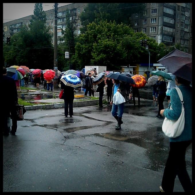 люди марно на зупинках чекають транспорту, треба йти в центр пішки